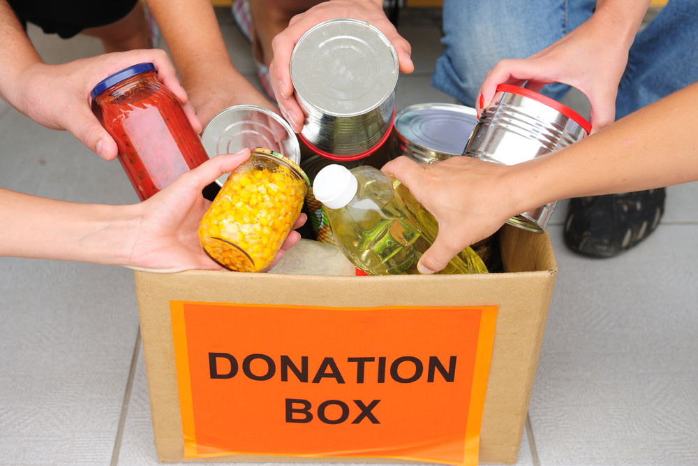 donation box with many hands putting food in