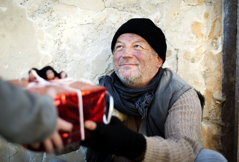 homeless man receiving red Christmas present