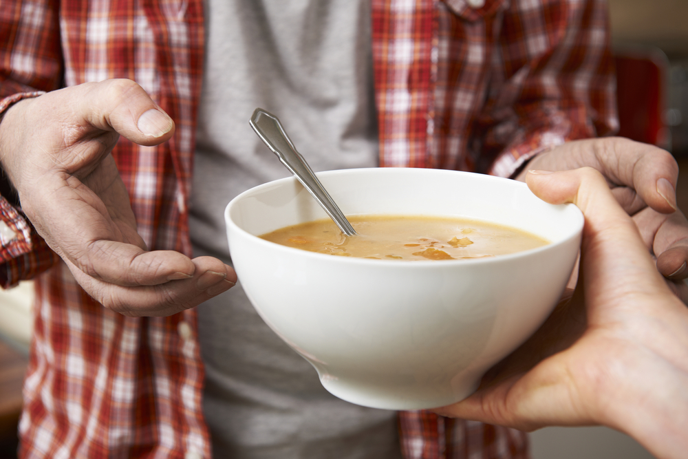 bowl of soup being handed to a homeless man