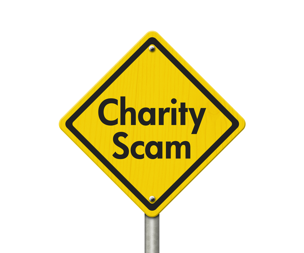 """A photo of a caution sign that reads """"charity scam."""""""