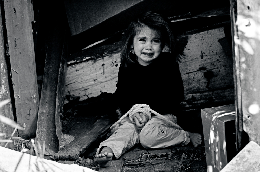 A photo of a young girl bound by rope, she is crying.