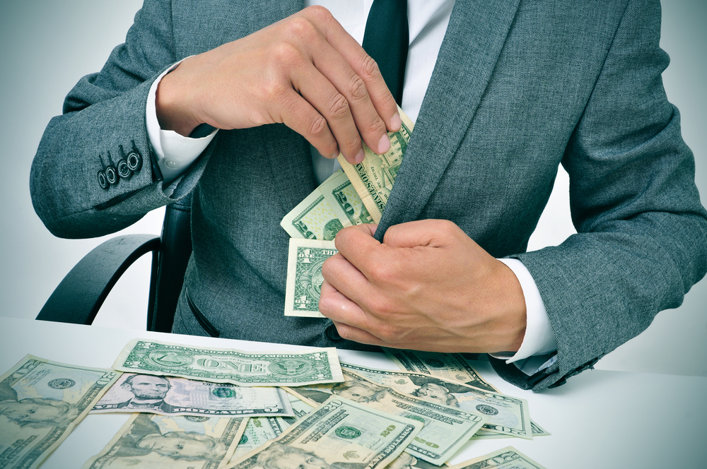 A photo of a man stuffing dollar bills into his business coat pocket.