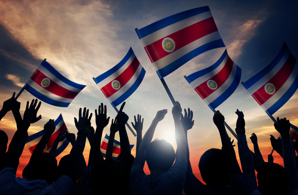 A photo of numerous people waving Costa Rican flags.