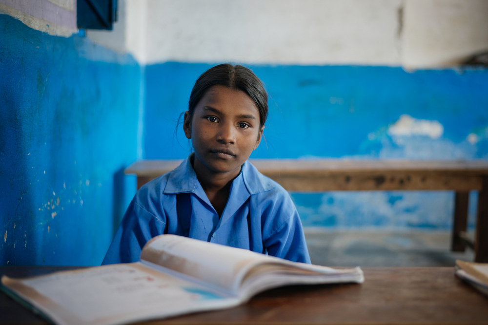 A photo of a young girl in a classroom with a book in front of her. The classroom is run-down.