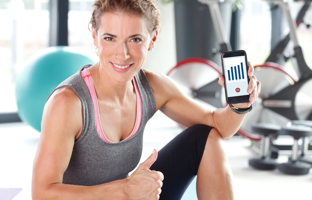 A photo of a young woman in workout attire tracking her fitness progress on her phone.