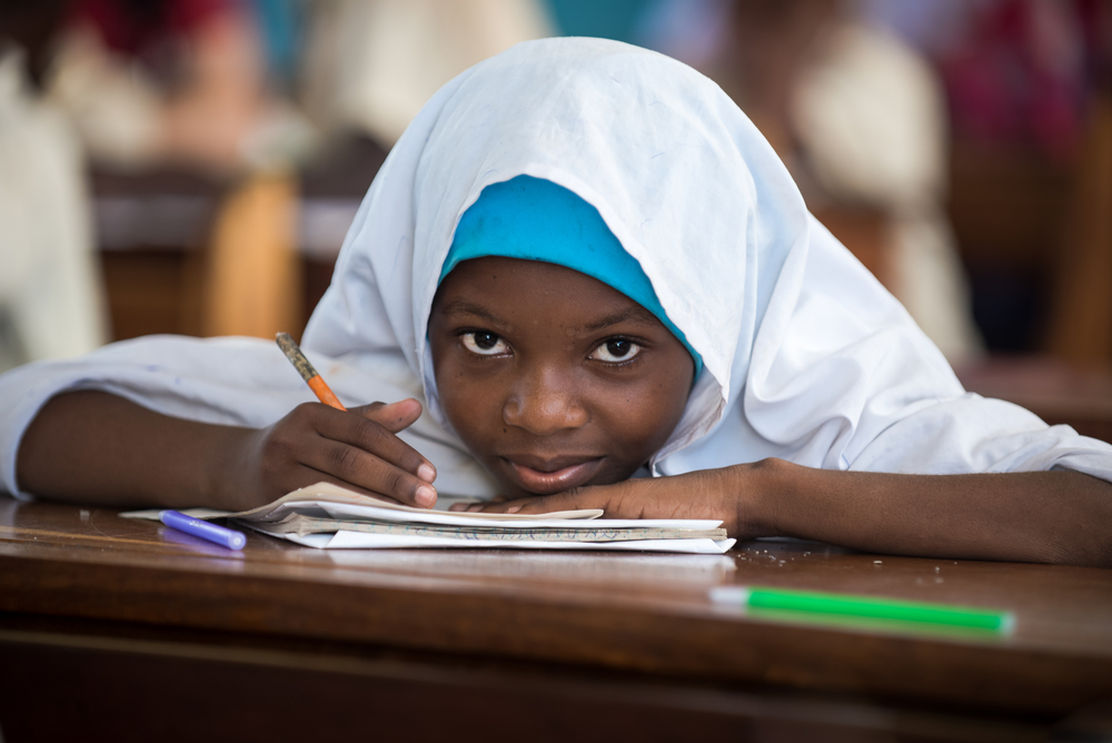 A close-up photo of a young Tanzanian girl writing in her notebook during class.