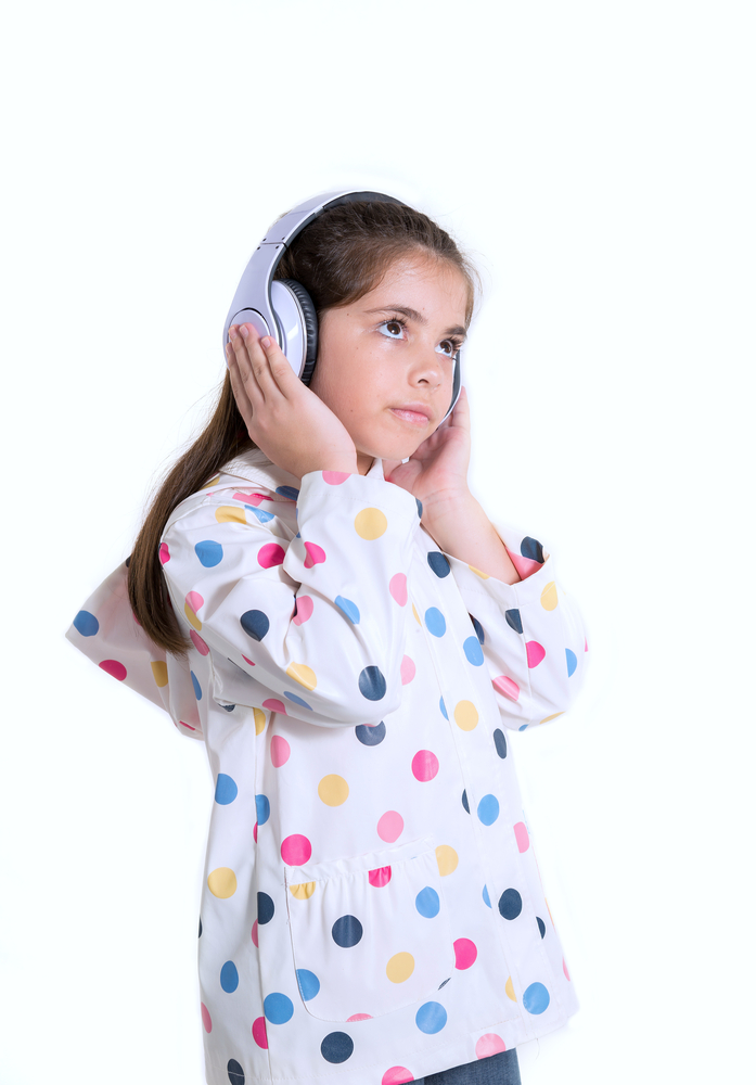 A photo of a little girl with headphones on.