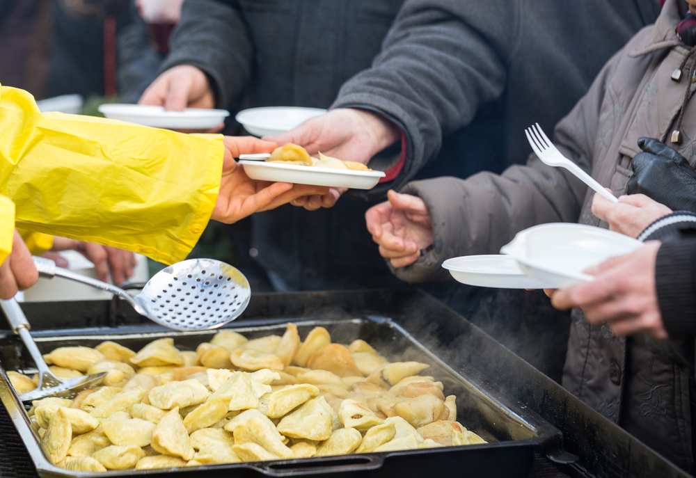 A photo of hot food being served to a line of homeless people.