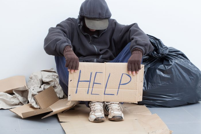 "A homeless African American man holds up a cardboard sign that reads, ""Help."""