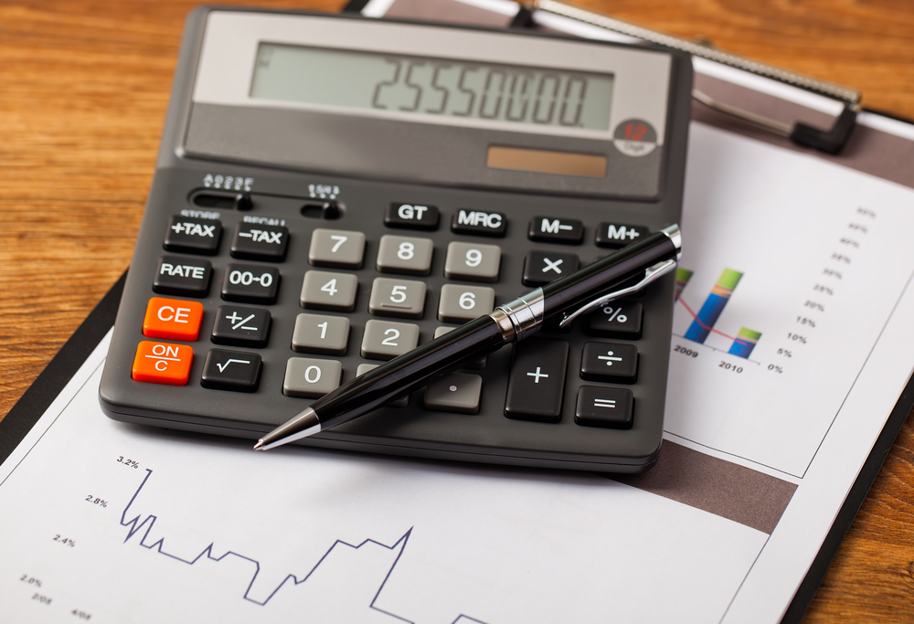 A calculator laying on top of a stack of revenue charts.
