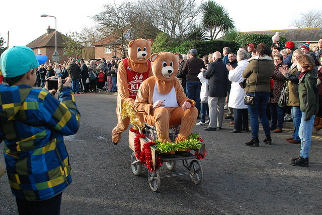 A photo of two people dressed up as bears. One is pushing the other in a stroller.