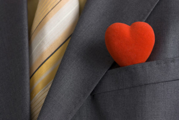 A man in a business suit. There is a red heart in his handkerchief pocket.