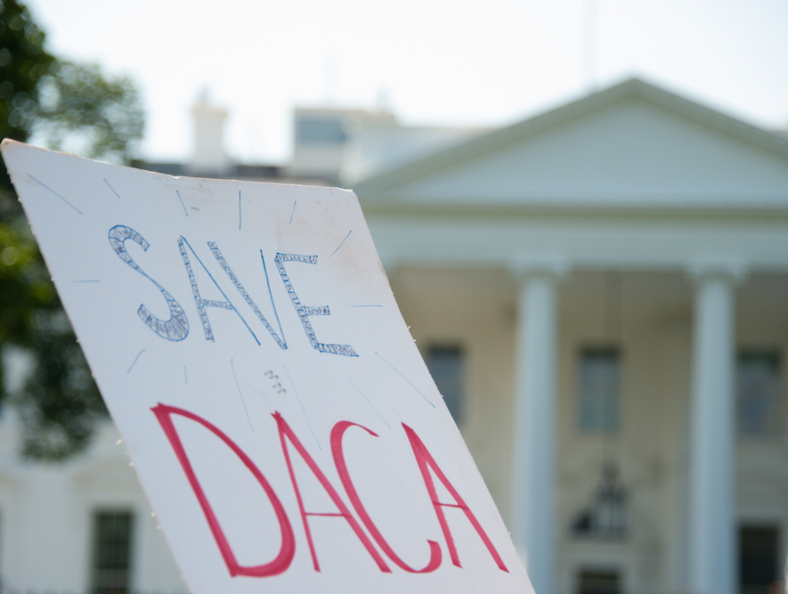 """A protestor stands outside of the White House with a sign that reads """"save DACA."""""""