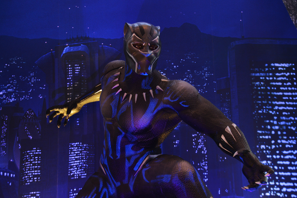Someone dressed up in a Black Panther suit stands in front of a city scape.