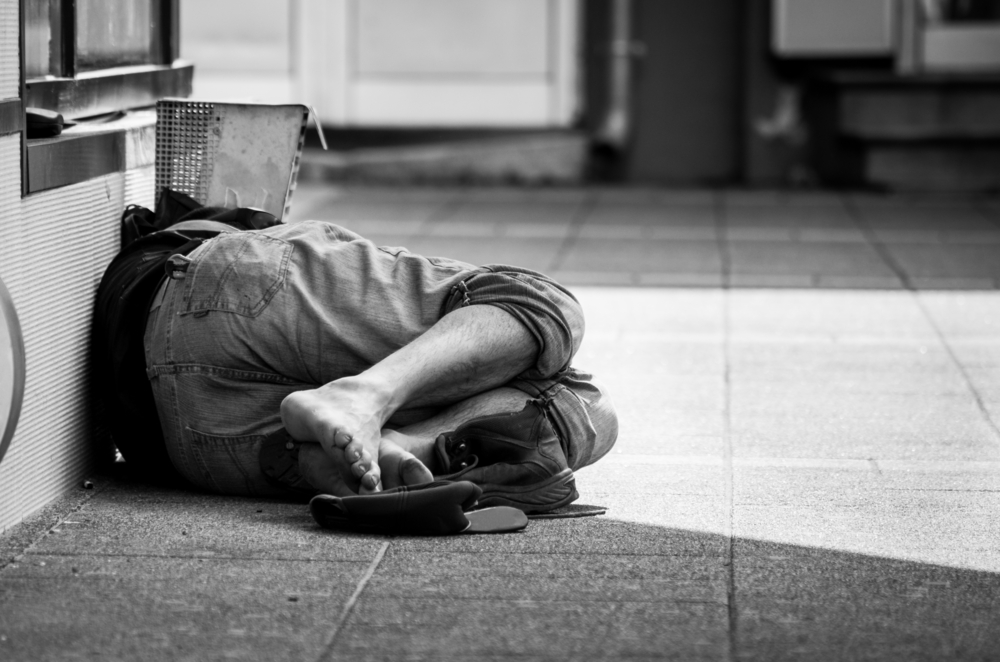 A homeless man without any shoes sleeping on the street.