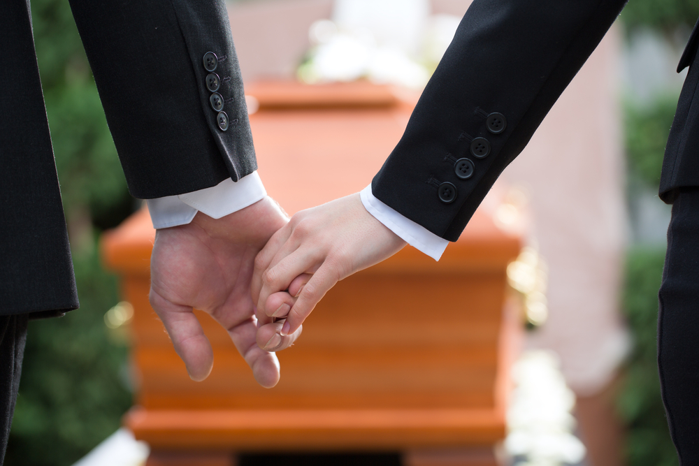 A couple holds hands in front of a coffin.