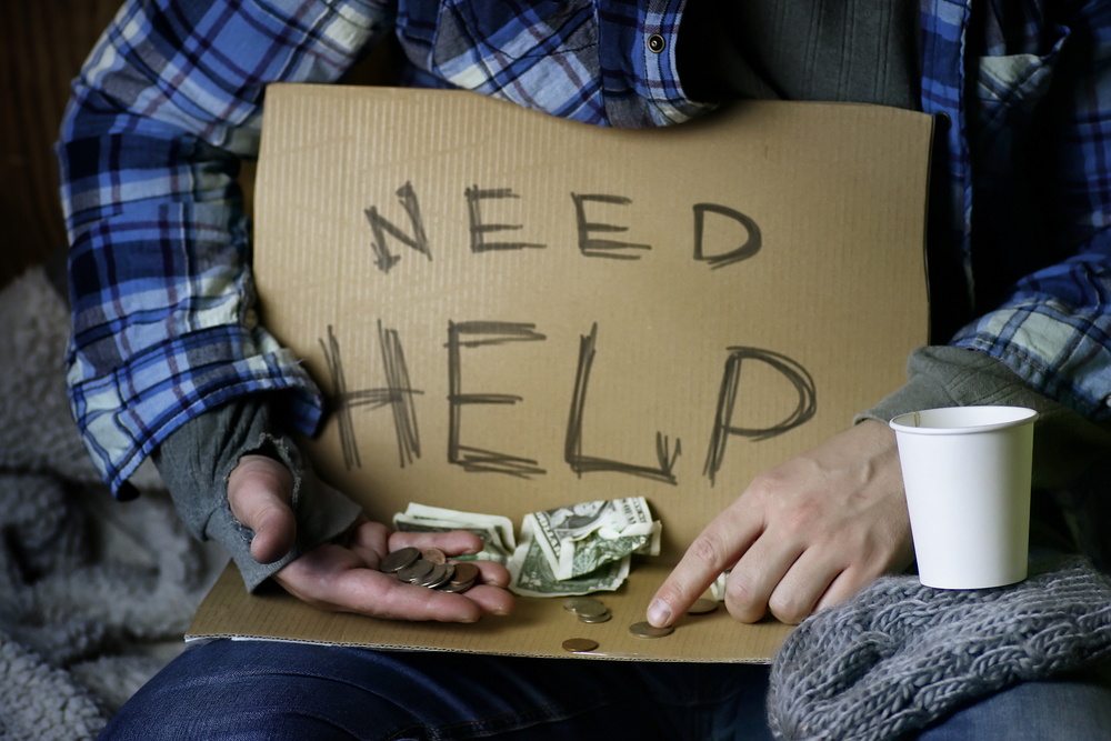 "A homeless man holding a cardboard sign that reads ""need help."""