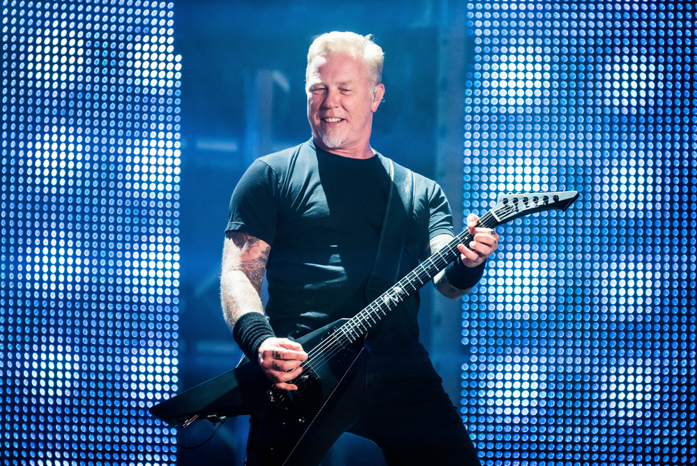 A photo of James Hetfield, lead singer of Metallica, playing guitar on stage.