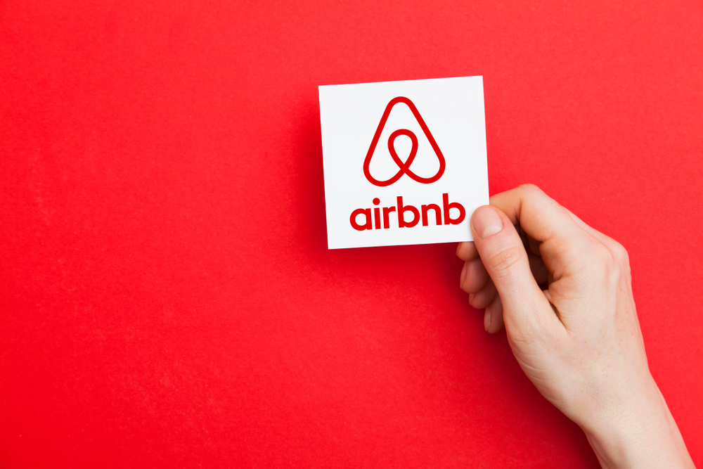 A person holding up the Airbnb logo.