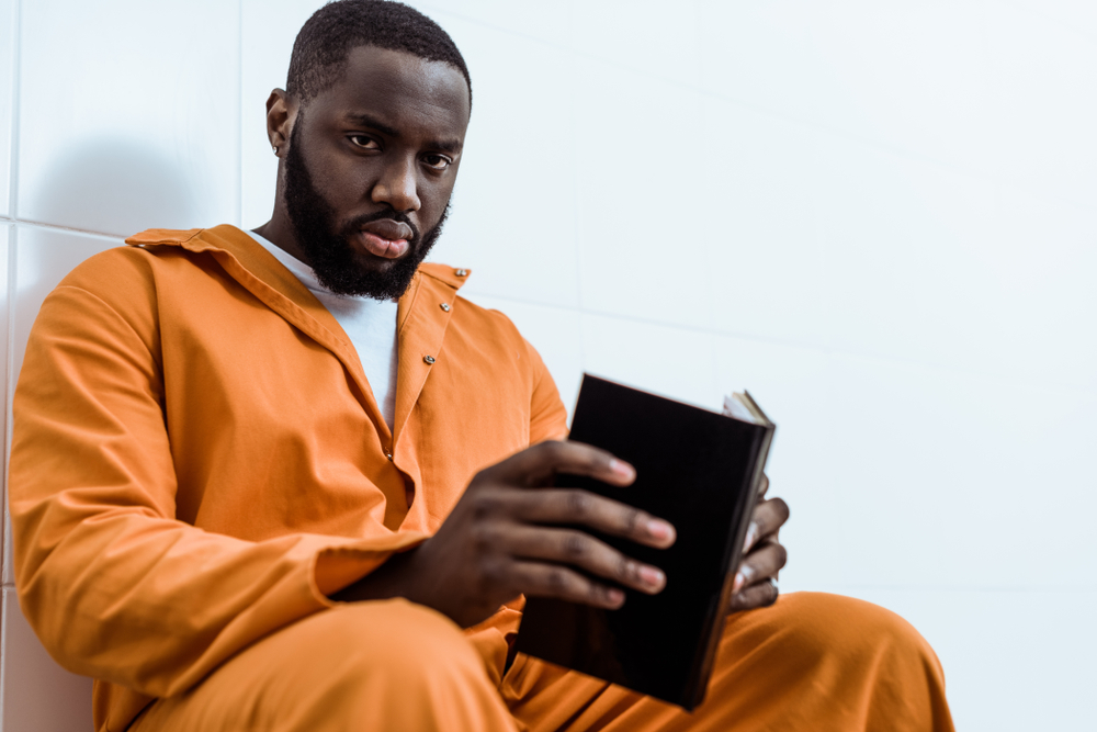 A prison inmate reading in his cell.