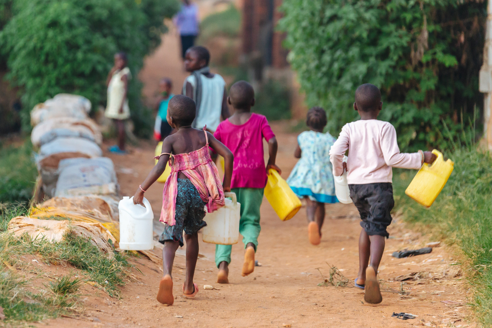 Children carrying water cans in Uganda.