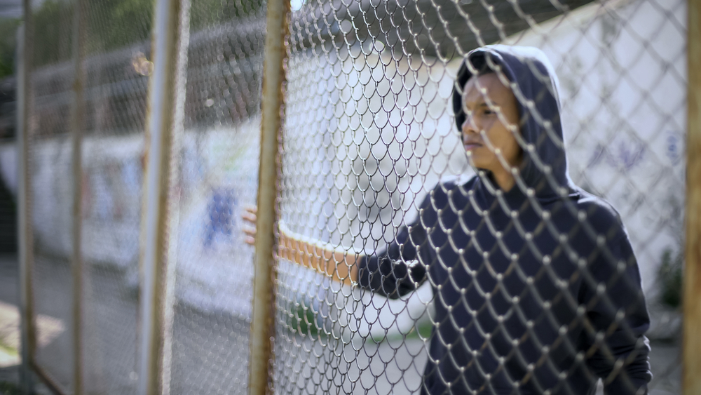 A migrant child behind a chain-link fence